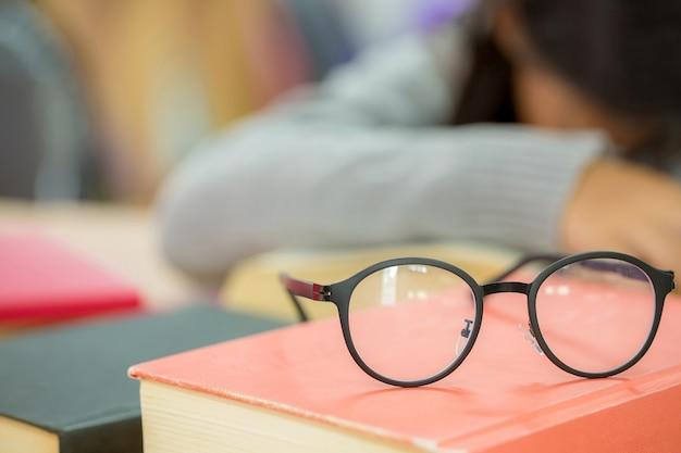 Feche acima dos vidros do olho na mesa de madeira e no livro de texto na biblioteca.