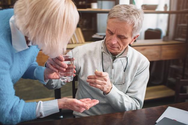 Feche acima e corte a vista de um homem recebendo algumas pílulas e um copo de água