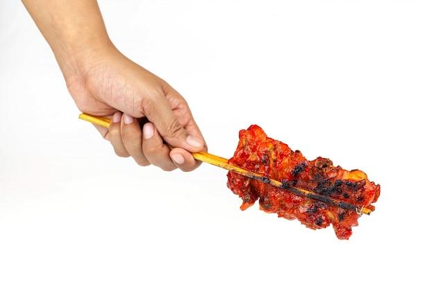 Feche acima e imagem isolada da mão segurando um frango grelhado