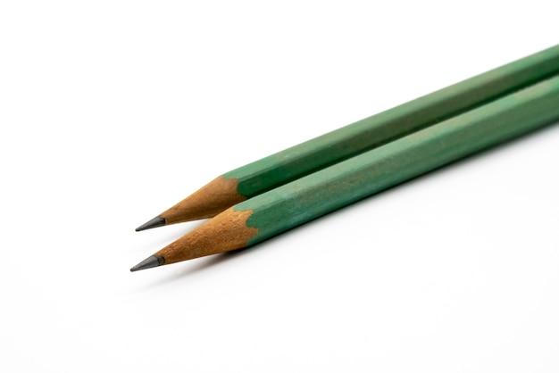 Feche acima em dois lápis verdes no fundo branco.