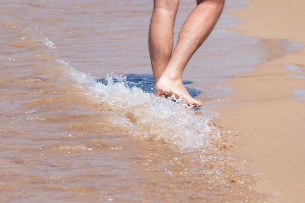 Feche acima em mover os pés de um homem que anda na praia.