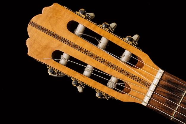 Feche acima em uma guitarra clássica feita de madeira.