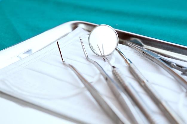 Feche acima, ferramentas profissionais do dentista na bandeja de aço inoxidável.