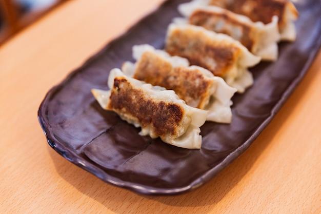 Feche acima gyoza (japonês frito bolinhos) servido com molho e óleo de gergelim.