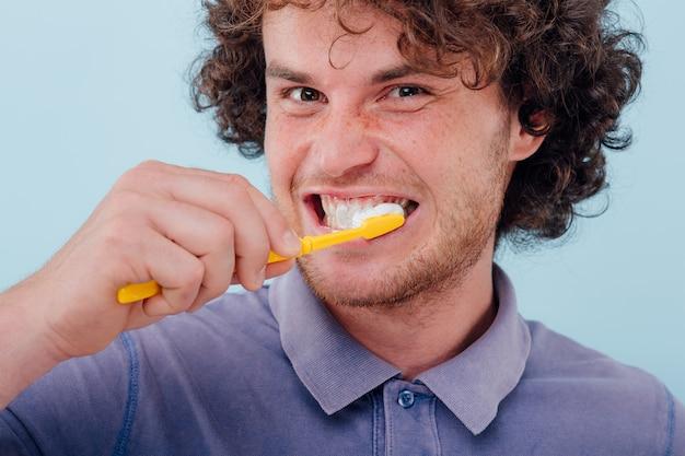 Feche acima, jovem escovando os dentes com pincel e cole.