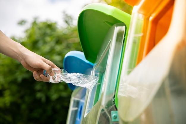 Feche acima, mão que coloca a garrafa de água potável plástica vazia torcida na lixeira em público.