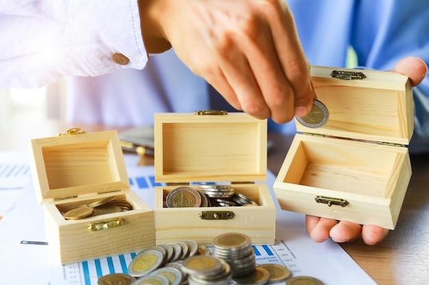 Feche acima, mão que põe a pilha das moedas do dinheiro no dinheiro da economia e no conceito crescente do negócio.