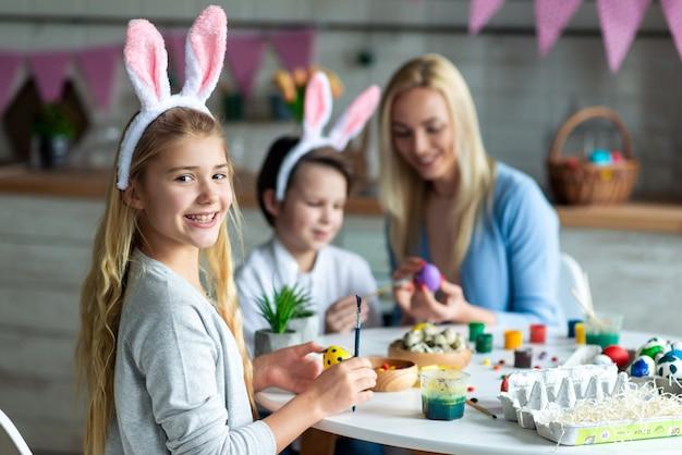 Feche acima, menina de sorriso que olha, pintando o ovo da páscoa.