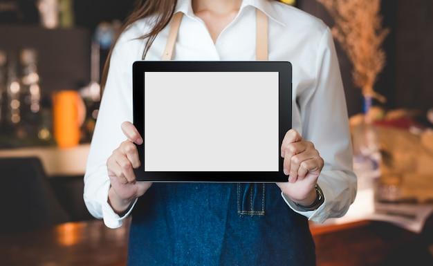 Feche acima no computador em branco que o barista mostra e mantém com duas mãos