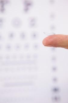 Feche acima no dedo segurando lentes de contato