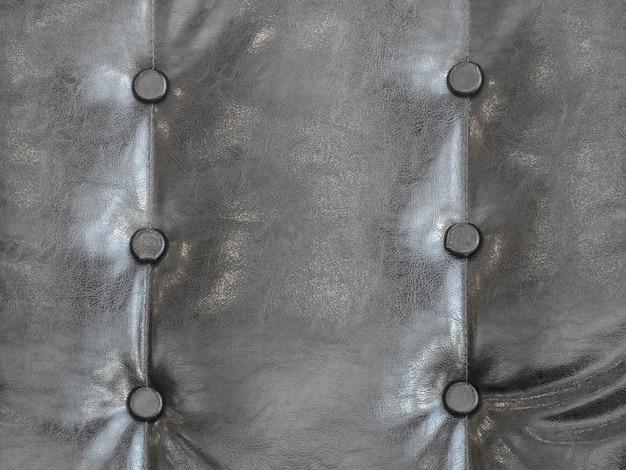 Feche acima no fundo de couro preto da textura da pele do sofá.