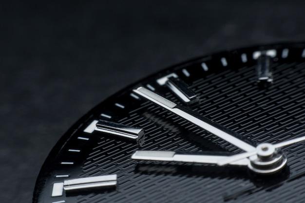 Feche acima no sentido horário no fundo preto da face do relógio. relógio de pulso em estilo retro
