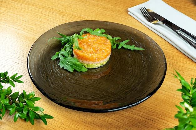 Feche acima no tartare de salmão com scaloop e rúcula. prato de peixe cru. comida deliciosa e saborosa em fundo de madeira.