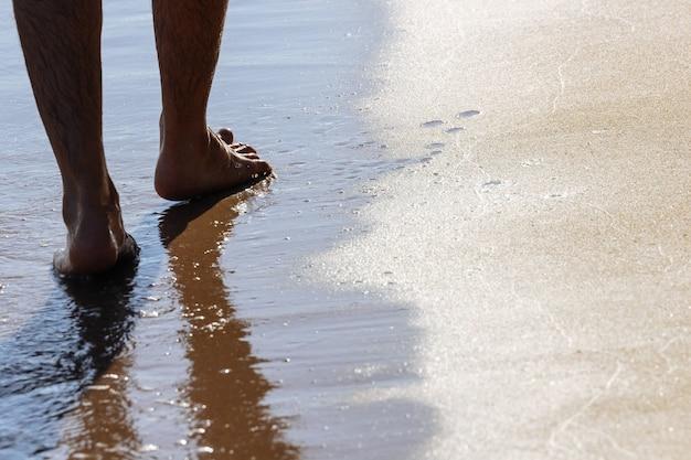Feche acima nos pés moventes de um homem que anda na praia na tarde em koh mak em trat, tailândia.