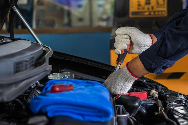 Feche acima, o serviço é povos é reparo um carro use uma chave de fenda e uma chave de fenda para trabalhar na garagem.