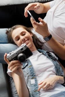 Feche amigos com câmera e telefone