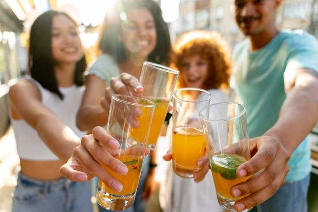 Feche amigos felizes com bebidas