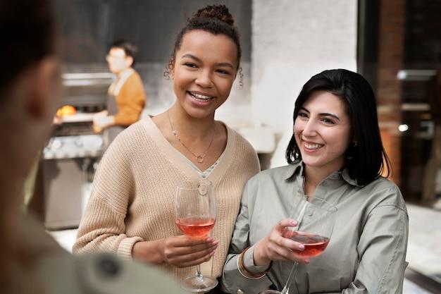 Feche amigos sorridentes com taças de vinho