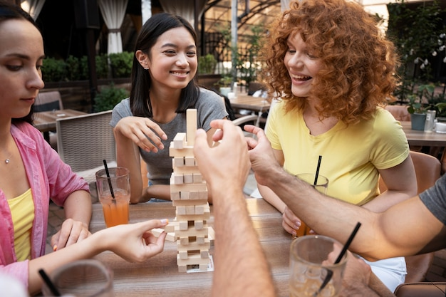 Feche amigos sorridentes jogando na mesa