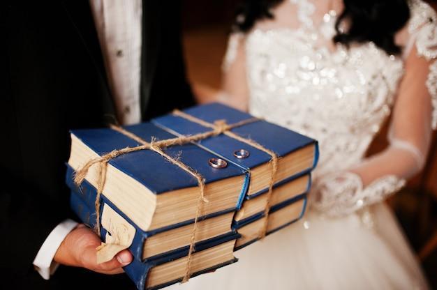 Feche as alianças de casamento em livros antigos na biblioteca nas mãos dos noivos.