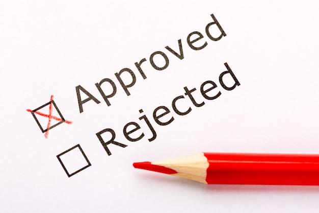 Feche as caixas de seleção aprovadas ou rejeitadas com lápis vermelho sobre papel branco.