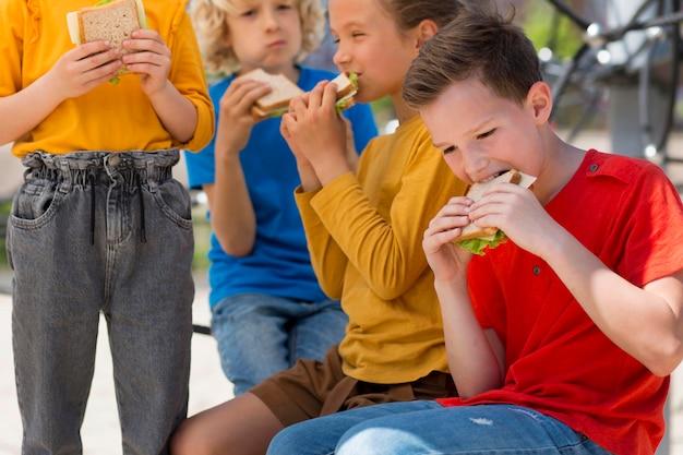 Feche as crianças com sanduíches