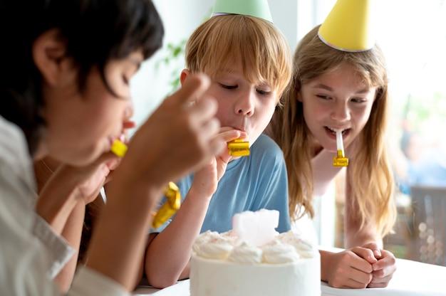Feche as crianças comemorando com bolo