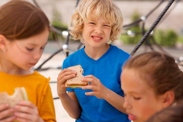 Feche as crianças comendo sanduíches juntas