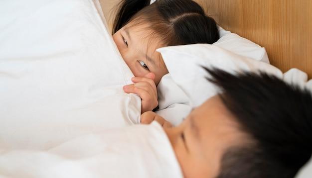 Feche as crianças deitadas na cama