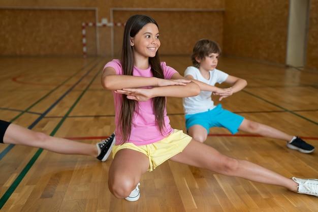 Feche as crianças se exercitando no ginásio da escola