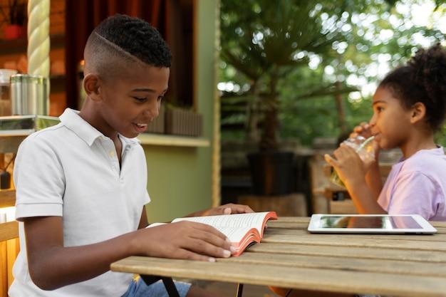 Feche as crianças sentadas à mesa com um livro e um tablet