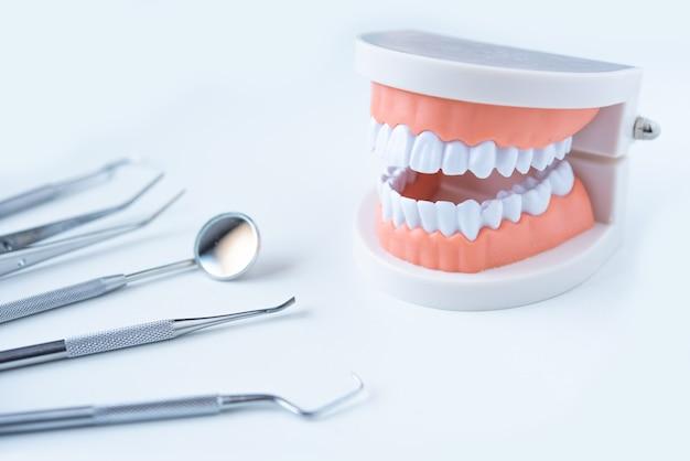 Feche as ferramentas do dentista para cuidar dos dentes na vista superior do fundo branco