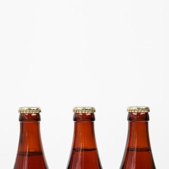 Feche as garrafas de cerveja no fundo branco, com espaço de cópia