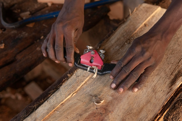 Feche as mãos afiando madeira