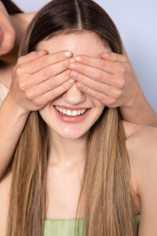 Feche as mãos cobrindo os olhos da mulher