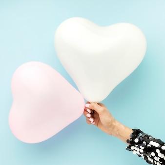 Feche as mãos com balões em forma de coração