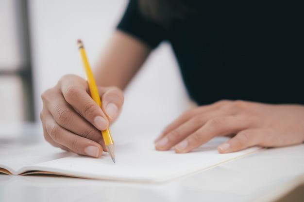 Feche as mãos com caneta escrevendo no caderno.