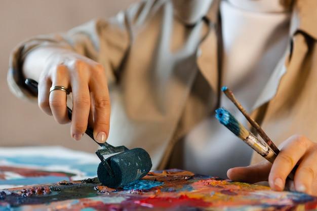 Feche as mãos com ferramentas de pintura
