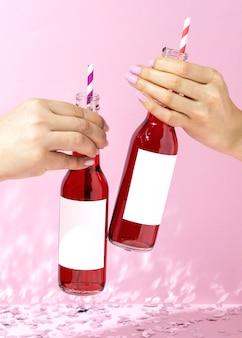 Feche as mãos com garrafas e canudos