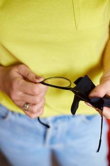 Feche as mãos cortadas de uma mulher limpando lentes de óculos pretos da moda com uma toalha, lenço de microfibra preto