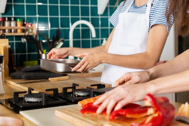 Feche as mãos cozinhando na cozinha