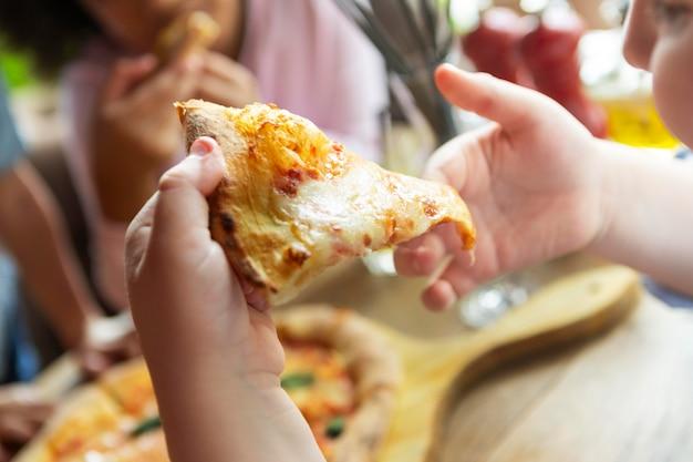 Feche as mãos da criança segurando uma fatia de pizza