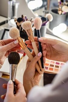 Feche as mãos da maquiadora estudando o cliente, escolhendo o pincel para aplicação de cosméticos