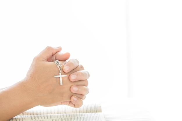 Feche as mãos da mulher com uma cruz nas mãos, orando a um deus. hora de oração no domingo.