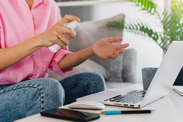 Feche as mãos da mulher em spray desinfetante anti-séptico no local de trabalho em casa trabalhando online no laptop