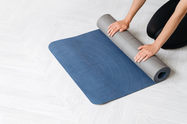 Feche as mãos da mulher preparando equipamentos de ginástica para aulas de ioga ou exercícios em casa ou na academia de esportes