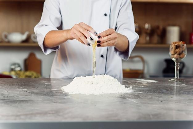 Feche as mãos da mulher quebrando o ovo sobre a pilha de farinha na mesa na cozinha. conceito de padaria em casa.