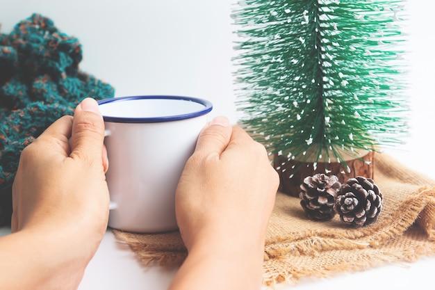 Feche as mãos da mulher segurando um copo de bebida quente. o inverno está chegando