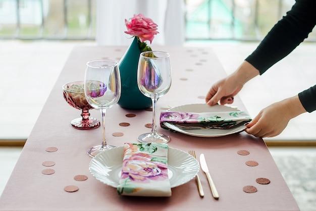 Feche as mãos da mulher, servindo a mesa de festa em suaves cores rosa com pratos brancos, copos de vinho, guardanapo floral têxtil. feliz aniversário ou chá de bebê para menina.