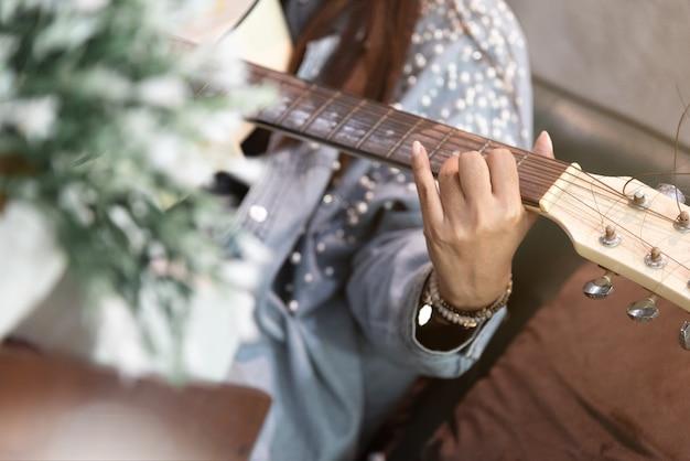 Feche as mãos da mulher tocando violão.
